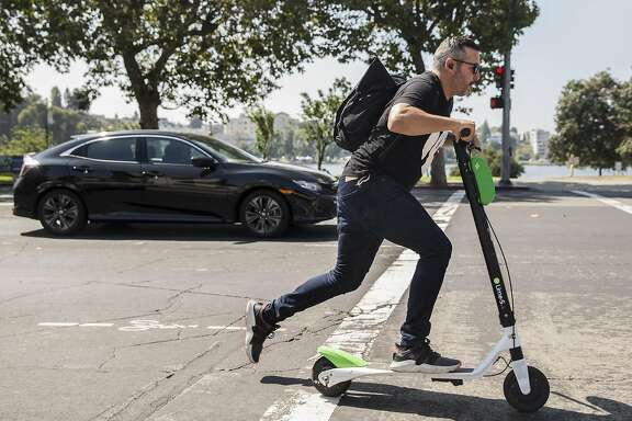 A man zips down Grand Avenue on a Lime electronic scooter near Lake Merritt in Oakland, Calif. Thursday, Aug. 16, 2018.
