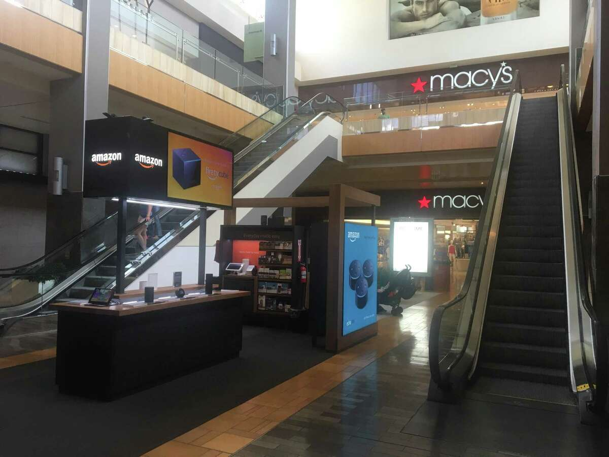 An Amazon kiosk is located outside the Macy's inside The Galleria shopping mall in Houston. Macy's is struggling to compete against online retailers like Amazon. Both companies are trying to move into the others' format.