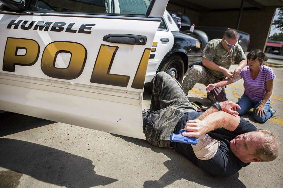 A wounded Jim Hammock, bottom, covers Kent Guidry as he treats Kathy McLaughlin, a victim of a domestic violence attack, during a training session for potential SWAT members Aug. 18, 2015, at the Humble Police Department. Photo: ANDREW BUCKLEY / Internal