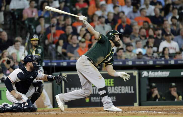 Oakland Athletics' Nick Martini hits a two-run double as Houston Astros catcher Max Stassi, left, reaches for the pitch during the fifth inning of a baseball game Thursday, July 12, 2018, in Houston. (AP Photo/David J. Phillip)