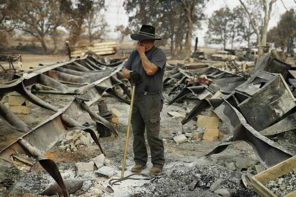 Ed Bledsoe, whose wife and great-grandchildren wer killed in the Carr Fire searches the remains of his home in Redding, Calif. Can climate change-induced disaster influence the 2020 election?