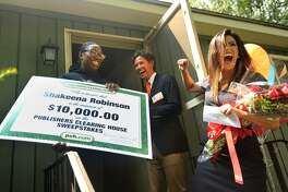 Shakeena Robinson of Milford is surprised by Publishers Clearing House Prize Patrol members Danielle Lam and Howie Guja Thursday.