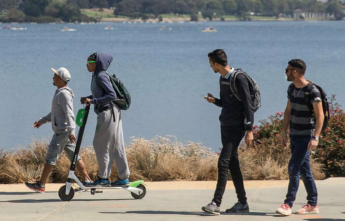 A woman rides a Lime electronic scooter around Lake Merritt in Oakland, Calif. Thursday, Aug. 16, 2018.