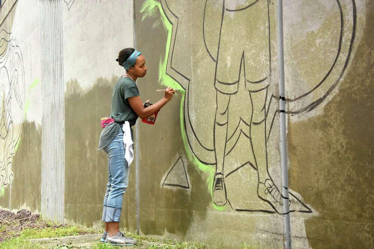 Liz Zunon works on the mural