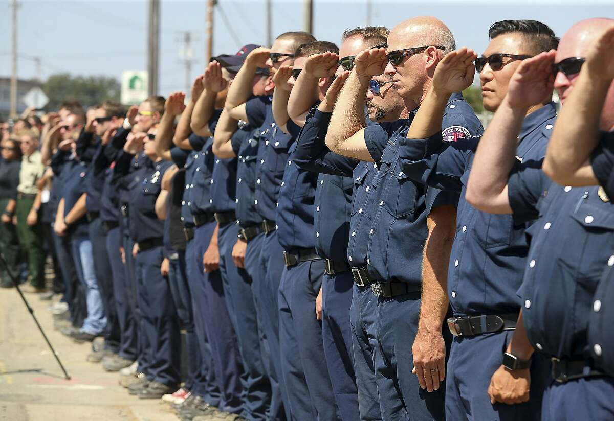 Firefighting personnel from various agencies salute as the procession for Battalion Chief Matthew Burchett travels along North State Street, in Ukiah, Calif., on Wednesday, Aug. 15, 2018. Burchett said goodbye to his wife and 7-year-old son in early August, volunteering to travel with fellow firefighters from Utah to help battle record-setting blazes in California. Burchett was hit by a falling tree and died Monday night while fighting the largest blaze in California history, the Mendocino Complex fire north of San Francisco. (Christopher Chung/The Press Democrat via AP)
