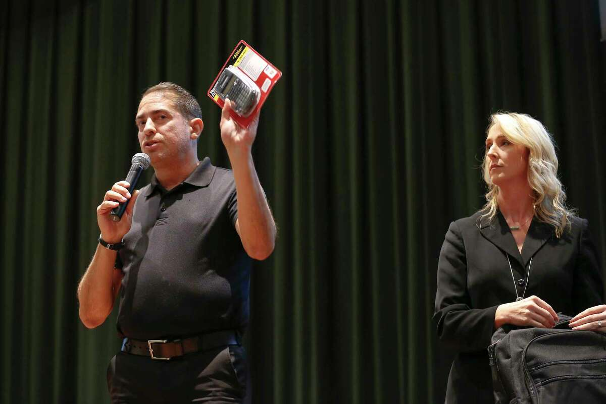 Garrett National Sales Security Sales Manger Joe Vazquez shows items for the ideal backpack with the help of Principal Racheal Blundell in the Santa Fe High School's auditorium Thursday, Aug. 16, 2018.