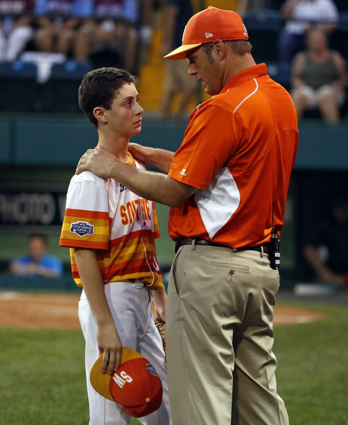 Houston, Texas pitcher Carter Pitts, left, listens to manager Dave Rook after after committing a fielding error, allowing a run to score, in the first inning of a baseball game against Coventry, Rhode Island in United States pool play at the Little League World Series tournament in South Williamsport, Pa., Thursday, Aug. 16, 2018. Texas won 3-1. (AP Photo/Gene J. Puskar)