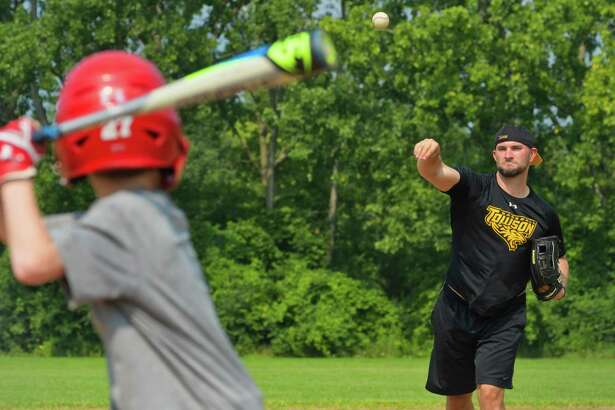 Former Major League Baseball outfielder Casper Wells of Baltimore, MD, throws a pitch to a child taking part in the week-long baseball camp Wells is running at the Schenectady Jewish Community Center on Thursday, Aug. 16, 2018, in Schenectady, N.Y. Wells graduated Schenectady High School in 2002 and following college he was drafted and played in Major League Baseball with Detroit, the Mariners and various other teams before leaving the MLB in 2015. (Paul Buckowski/Times Union)