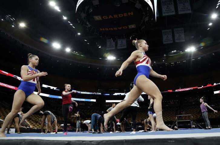 Ragan Smith, right, warms up with other competitors Wednesday in advance of the USA Gymnastics national championships in Boston. The meet opened Thursday under a cloud of continued legal action.