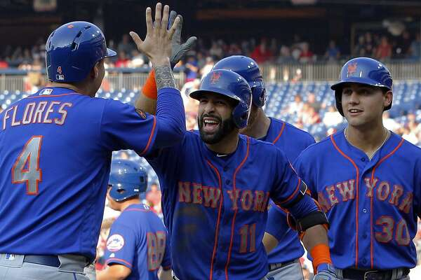 New York Mets' Jose Bautista, center, high-fives Wilmer Flores after Bautista hit a grand slam during the fifth inning of a baseball game against the Philadelphia Phillies, Thursday, Aug. 16, 2018, in Philadelphia. (AP Photo/Tom Mihalek)
