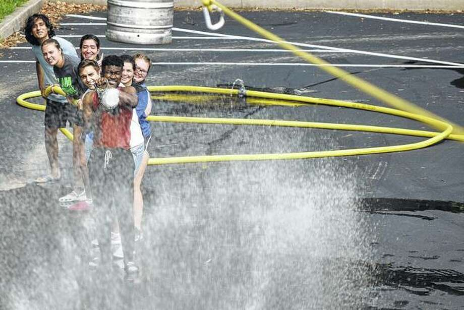 Illinois College resident assistants compete Thursday in the Firemen's Rodeo after spending time practicing fire drills and fire extinguisher training. The teams tried to use the hose to push a barrel to the opposing team's side of the field. Photo:       Samantha McDaniel-Ogletree | Journal-Courier