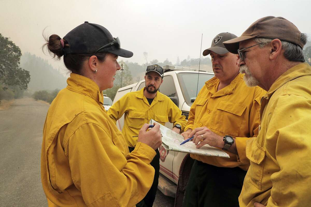 L-R, Australian firefighter Beverly Gardiner, New Zealand firefighter, Thomas Harre, Australian firefighter Justin Pinson, and Peter Tolosano, Operations Branch Manager of California Interagency Incident Management gather to plan their planned attack on the head of the Mendocino Complex Fire in the Mendocino National Forest east of Ukiah, Calif., on Tuesday, August 14, 2018.