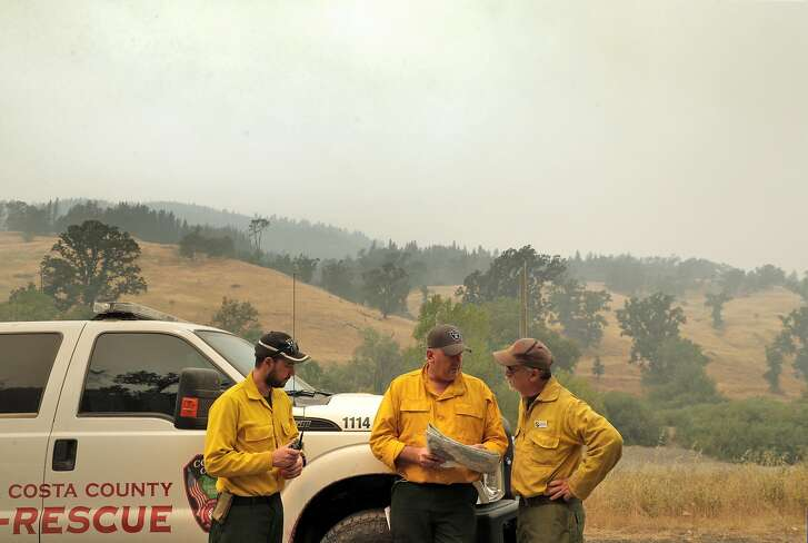 New Zealand firefighter, Thomas Harre, left, Australian firefighter Justin Pinson, center, and Peter Tolosano, the operations branch director for CA Interagency Incident Management, plan their approach to battling the head of the Mendocino Complex Fire in the Mendocino National Forest east of Ukiah, Calif., on Tuesday, August 14, 2018.