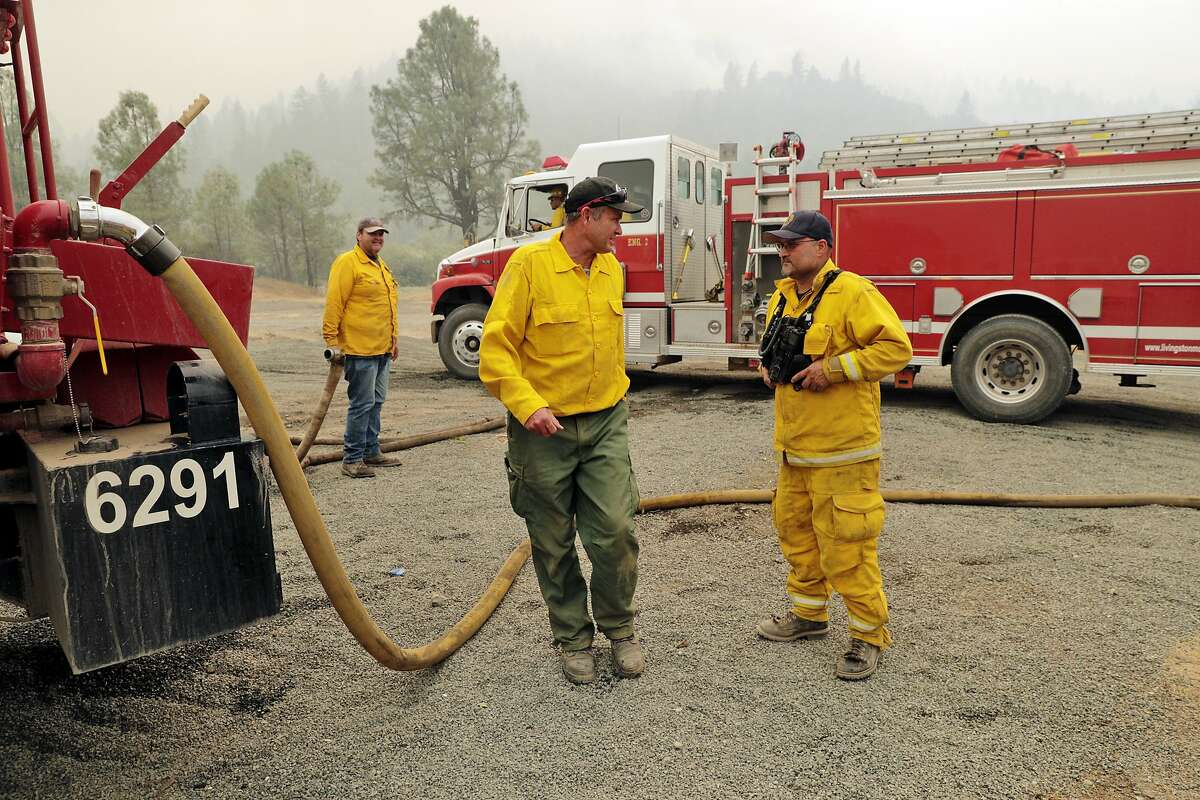 New Zealand firefighter Phil Muldoon, left, coordinates water refills with Bernardo Gonzalez, right, of the Redwood Valley Fire Department, in the Mendocino National Forest while fighting the Mendocino Complex Fire east of Ukiah, Calif., on Tuesday, August 14, 2018.