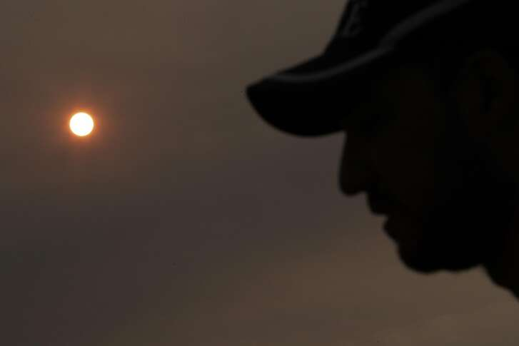 Firefighter Thomas Harre stands silhouetted by the sun, colored by the heavy smoke in the air, at the Incident Command Post before heading out to the Mendocino Complex Fire in Ukiah, Calif., on Tuesday, August 14, 2018.