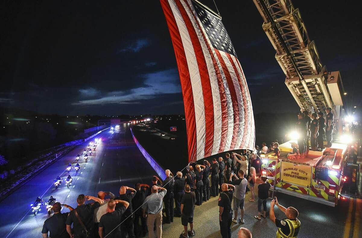 Utah firefighter Matt Burchett, 42, who died fighting a wildfire in California, is honored by a detail along Murray Parkway as his body is returned home, traveling along Interstate 215 after being flown to the Utah Air National Guard in Salt Lake City, Wednesday, Aug. 15, 2018. Burchett was hit by a falling tree and died Monday night while fighting the largest blaze in California history, the Mendocino Complex fire north of San Francisco. (Francisco Kjolseth/The Salt Lake Tribune via AP)