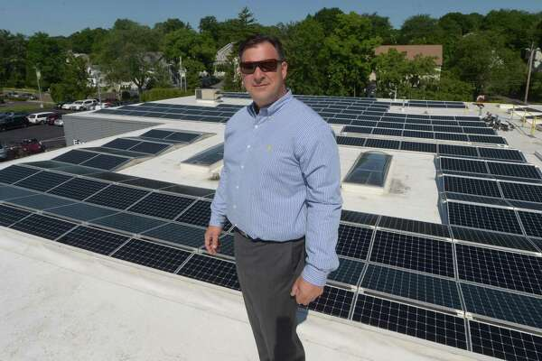 Gregg Miller, co-owner of the Miller Nissan dealership stands in front of the new solar-energy array on the dealership's roof at 930 Kings Highway East in Fairfield, Conn., on July 18, 2018.