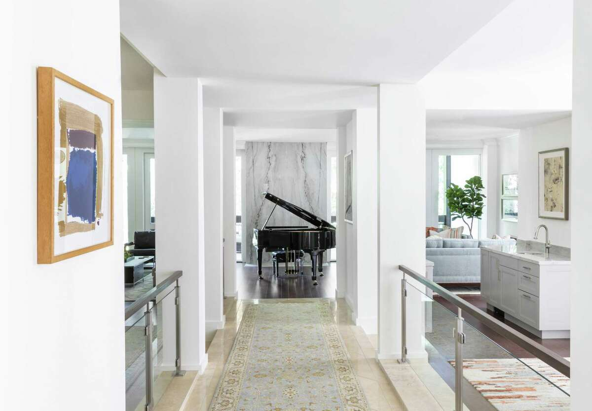 """The center of the home's main floor is an elevated hallway that gives all of the rooms off of it a """"sunken"""" feel because you step down into them. Walls that defined the rooms were removed, and short glass panels with wooden hand rails serve as a transparent separation."""