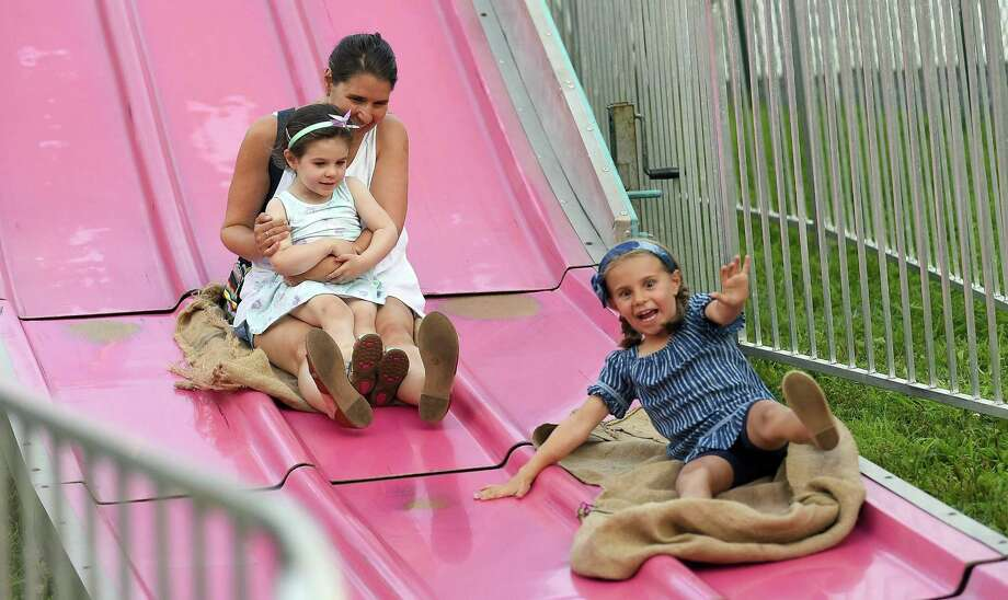Cecilia Morey, 5, of Fairfield races her mom Jessie and sister Natalie, 3, down the Fun Slide as they enjoy the annual St. Roch's Feast in Greenwich on Aug. 8. Photo: Matthew Brown / Hearst Connecticut Media / Stamford Advocate