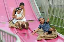 Cecilia Morey, 5, of Fairfield races her mom Jessie and sister Natalie, 3, down the Fun Slide as they enjoy the annual St. Roch's Feast in Greenwich on Aug. 8.