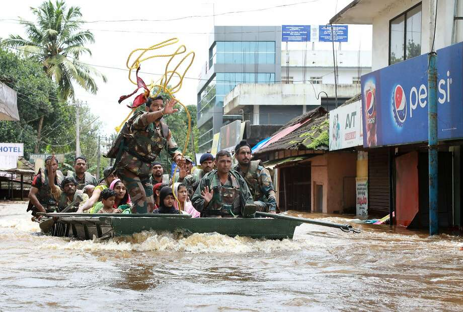 Indian army personal evacuate local residents in a residential area at Aluva in Ernakulam district, in the Indian state of Kerala, on August 17, 2018. - Troop reinforcements stepped up desperate rescue attempts in India's flood-stricken Kerala state on August 17 after more than 100 bodies were found in a day and a half, taking the crisis death toll to at least 164. (Photo by - / AFP)-/AFP/Getty Images Photo: -, AFP/Getty Images