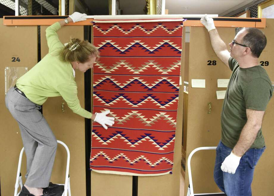 """A Continuous Thread: Navajo Weaving Traditions,"" which opens Saturday at the Bruce Museum, traces the history of the Navajo weaving tradition from the earliest Mexican-inspired Saltillo serapes circa 1880 to mid-20th century pictorial rugs. It features a dozen items from the museum's Native American ethnographic collection — some of which have never been publicly exhibited. Registrar and Exhibit Curator Kirsten Reinhardt, left, and Collections Manager Timothy Walsh show a traditional eyedazzler pattern rug, dated between 1965 and 1985, from the collections storage area. For more info, call 203-869-0376 or visit brucemuseum.org Photo: Tyler Sizemore / Hearst Connecticut Media / Greenwich Time"