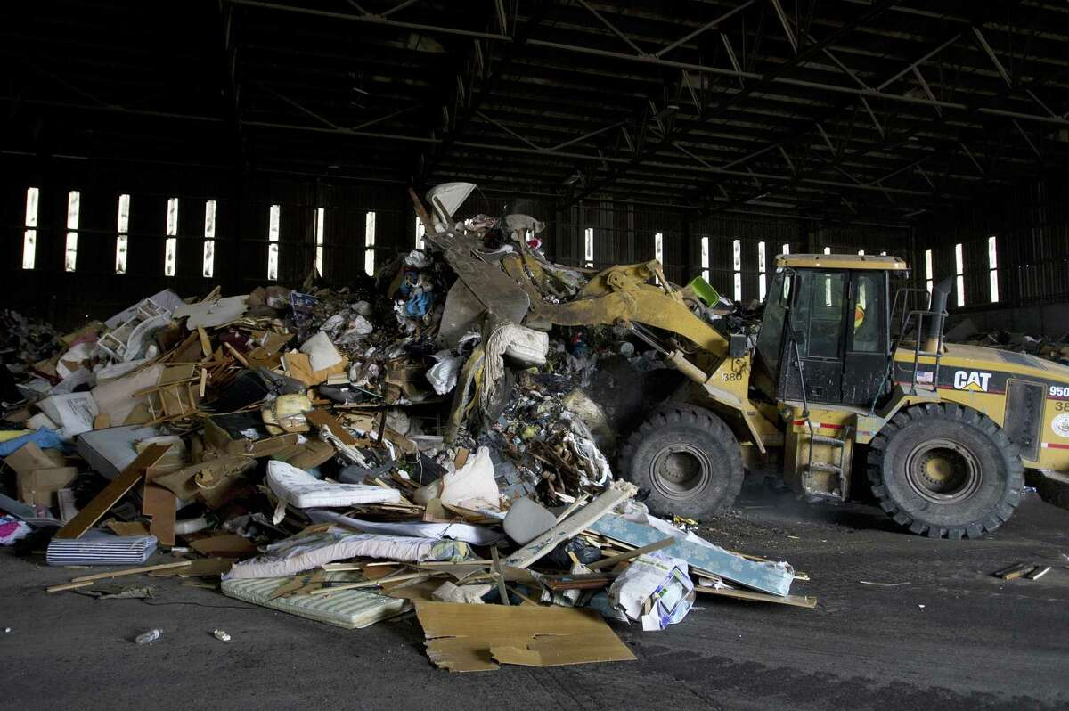 A large pile of garbage gets condensed by a front loader at the transfer station on Harborview Avenue on Thursday. Many recyclables once discarded at Katrina Mygatt Recycling Center now are being brought to the dump for sorting.