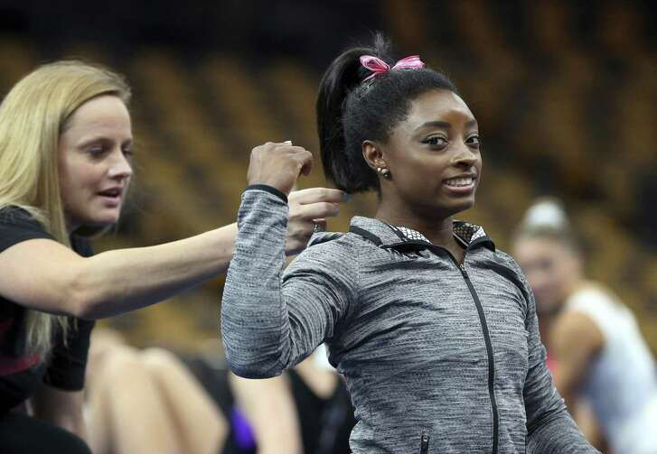 Simone Biles has her hair adjusted by her coach, Cecile Canqueteau-Landi, during a training session at the U.S. Gymnastics Championships, Wednesday, Aug. 15, 2018, in Boston. (AP Photo/Elise Amendola)