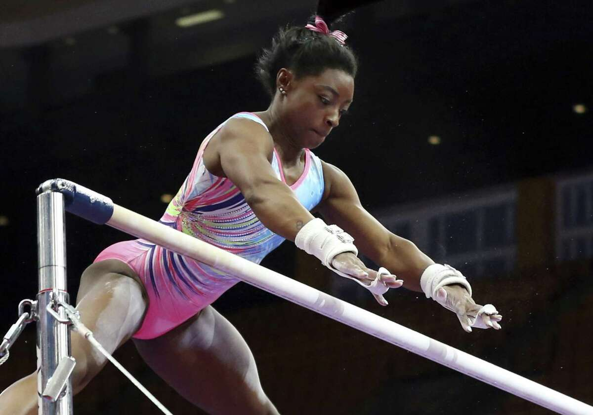 Simone Biles practices on the uneven bars during a training session at the U.S. Gymnastics Championships, Wednesday, Aug. 15, 2018, in Boston. (AP Photo/Elise Amendola)