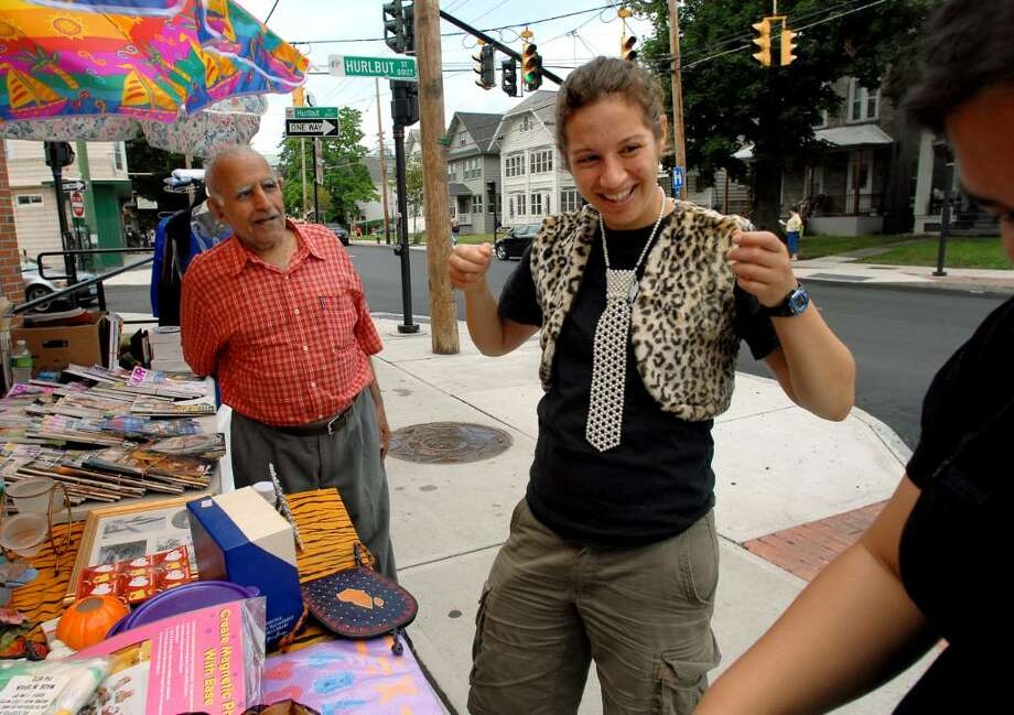 Lauren Sirkin of Albany, center, adds a pearl tie to her faux leopard vest as she hunts for treasures during the Delaware Avenue Street Fair and Community Garage Sale on Saturday inAlbany. (Cindy Schultz / Times Union) Photo: CINDY SCHULTZ / 00009423A