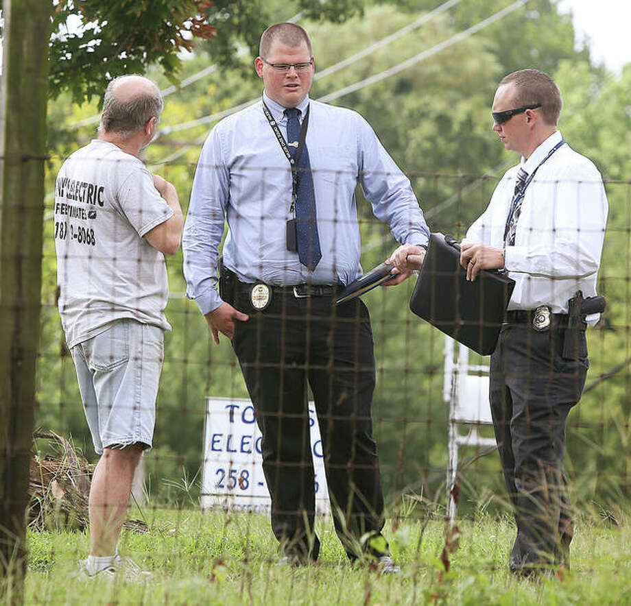 Members of the Major Case Squad interview a resident Friday, left, who lives near where a 24-year-old man was shot in a home invasion late Thursday night on South Oak Street in Cottage Hills. The man later died in a St. Louis hospital. Photo:       John Badman | The Telegraph