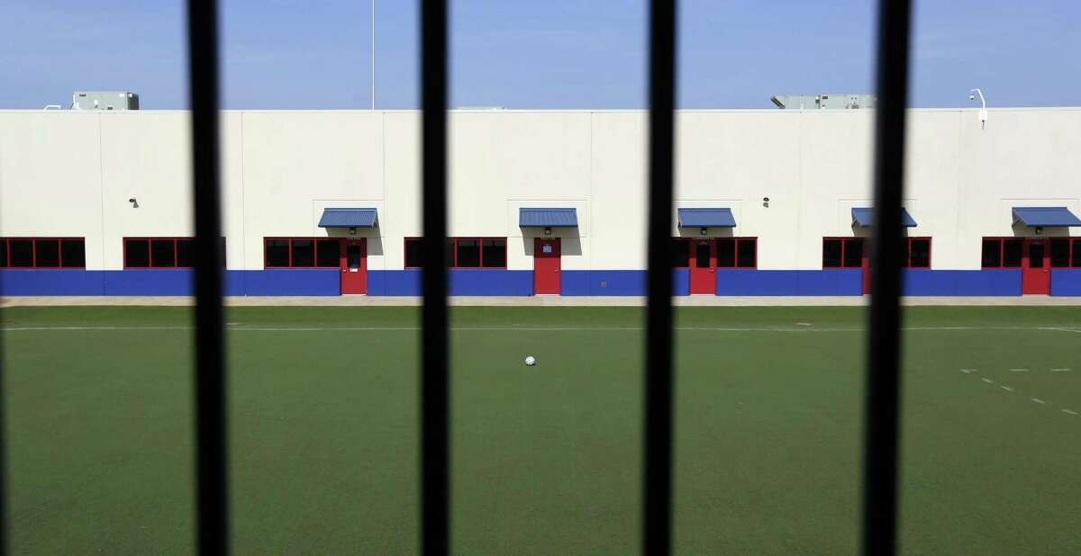 This July 31, 2014, file photo, shows an artificial turf soccer field in the middle of the Karnes County Residential Center in Karnes City. The immigration detention facility was retooled to house adults with children who have been apprehended at the border. It now houses reunited fathers and sons. A disturbance occurred there Wednesday and 16 fathers were taken to a jail in Pearsall. They were returned to the facility Thursday night, officials said. No injuries were reported.