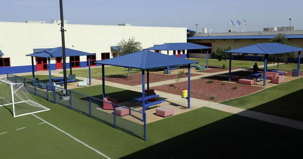 In this July 31, 2014, file photo, a courtyard is seen at the Karnes County Residential Center in Karnes City. The facility now houses reunited fathers and sons. A disturbance occurred Wednesday afternoon at the facility that now houses reunited fathers and sons. Officials said 16 fathers were taken to a jail in Pearsall overnight but were returned to the facility Thursday evening.
