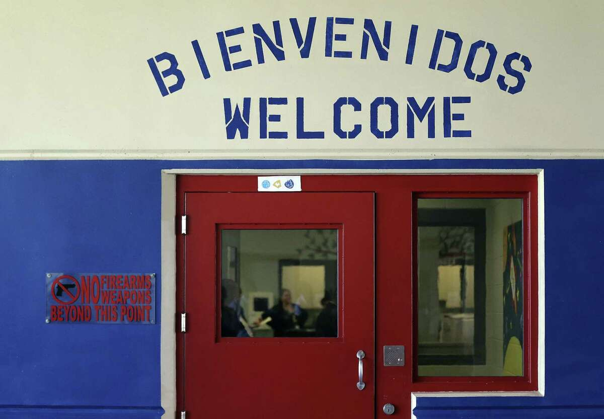 this July 31, 2014, file photo, a Spanish and English welcome sign is seen above a door in a secured entrance area at the Karnes County Residential Center in Karnes City. The facility now houses reunited fathers and sons. A disturbance occurred there Wednesday and 16 fathers were taken to a jail in Pearsall. They were returned to the facility Thursday night, officials said.