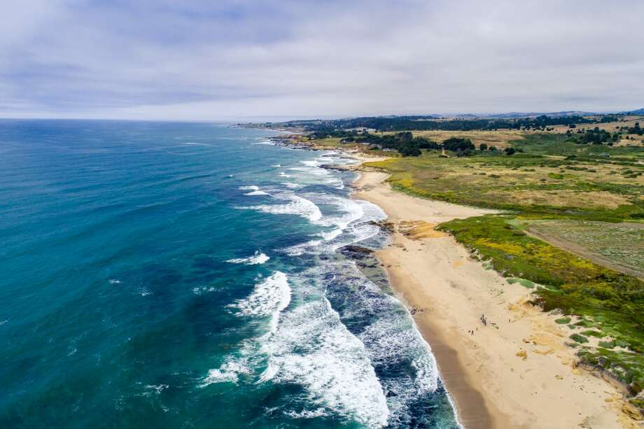 The 414-acre Bolsa Point Ranch in Pescadero, Calif., offers the opportunity for a true California lifestyle with verdant farmland rolling toward rugged cliffs overlooking secluded beaches and multiple historic farm buildings including a barn. Photo: Drone Cowboys