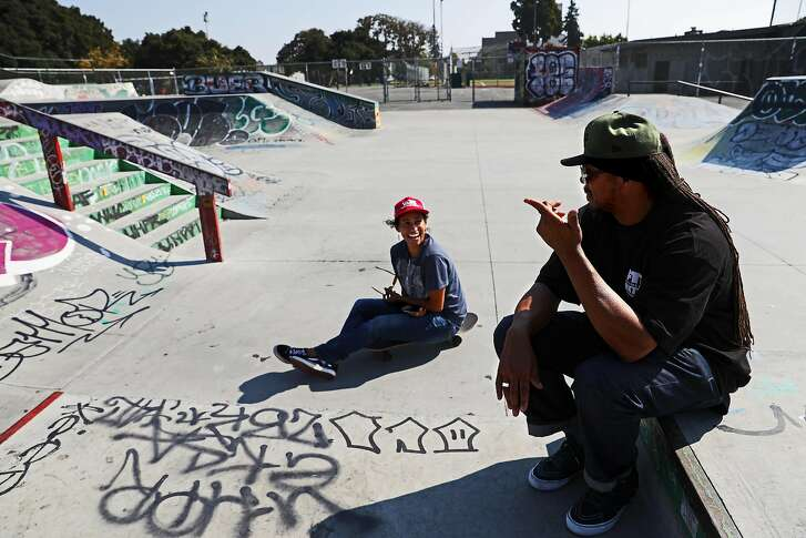 """Keith �K-Dub� Williams converses with skateboarder Vanessa Touset at Town Park skatepark in West Oakland, Calif., on Wednesday, August 15, 2018. Williams is a dreadlocked, 55-year-old 6�5� artist, educator, mentor, and former skateboarder who founded Town Park, a skatepark located at DeFremery Park. �I think my role in it in being that liaison and being that Pied Piper on that piece is really cemented what an artist can give back to a community,"""" Williams said. """"I think the fact that we were able as young people participating in elements in helping shape Town Park and the culture is another act of what the power of young people can do.�"""