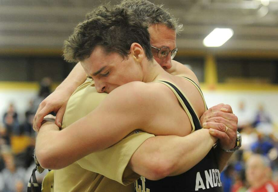 Trumbull Head Coach Charlie Anderson hugs his son Ben after winning the CIAC Class LL Wrestling Tournament by defeating Cheshire's Scott Tomlinson in Trumbull, Conn. on Saturday February 19, 2011. Photo: Christian Abraham / ST / Connecticut Post