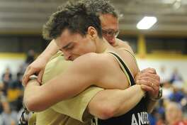 Trumbull Head Coach Charlie Anderson hugs his son Ben after winning the CIAC Class LL Wrestling Tournament by defeating Cheshire's Scott Tomlinson in Trumbull, Conn. on Saturday February 19, 2011.