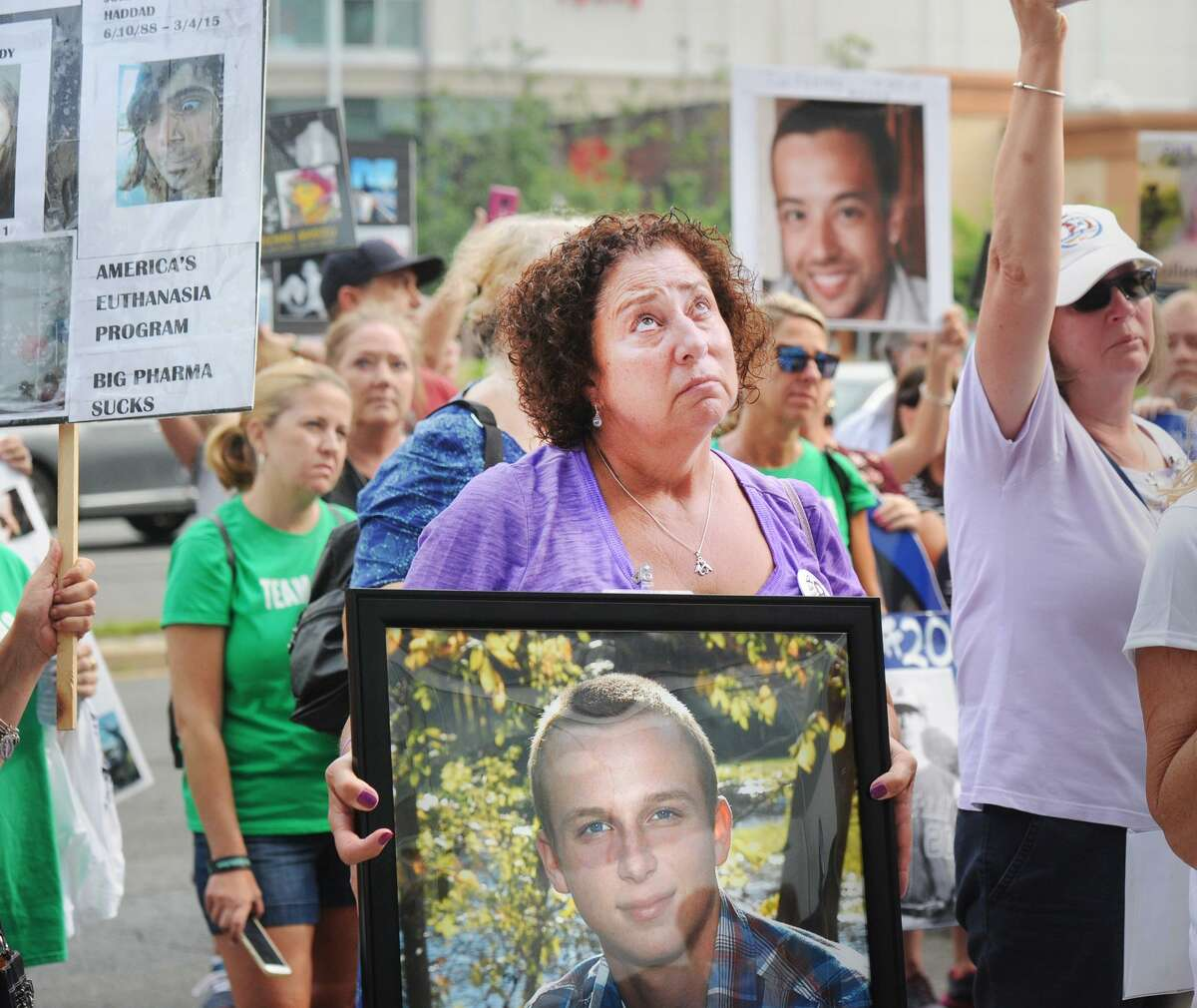 Nancy Tobin, of Hudson, Mass., looks skyward as she holds a poster photo of her late son, Scott Tobin, who died in 2017 and who she said was a victim of the opioid crisis, during a protest against Purdue Pharma, the maker of the opioid OxyContin, outside Purdue Pharma's headquarters at 201 Tresser Blvd., in Stamford, Conn., on Friday, August 17, 2018. Protesters said OxyContin is highly addictive and can be directly blamed for the opioid-related deaths of their loved ones.