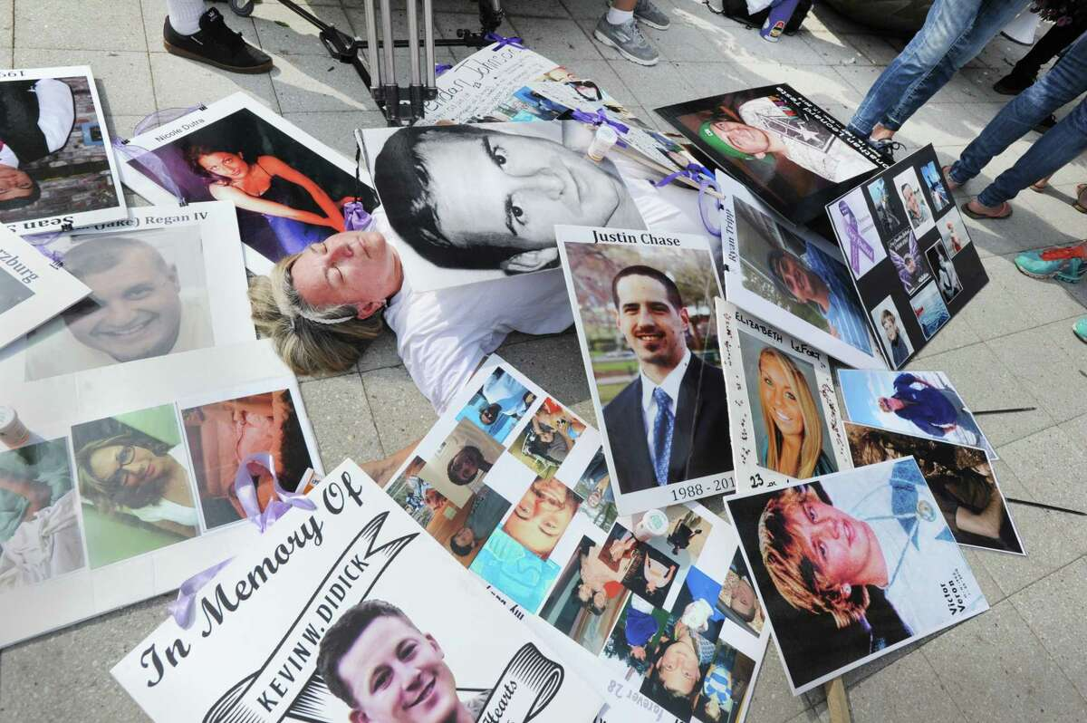 Joan Peters-Gilmartin, of Falmouth, Mass., lays down on the sidewalk surrounded by photos of victims of the opioid crisis, including her late son, Cory Gilmartin, who died in 2014 of a heroin overdose during a protest against OxyContin maker Purdue Pharma, outside the company's headquarters at 201 Tresser Blvd., in downtown Stamford, Conn., on Friday, Aug. 17, 2018.
