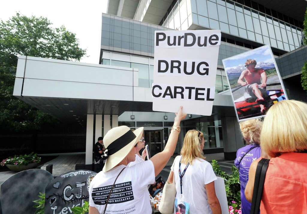 """Purdue Drug Cartel,"" reads the sign of a woman attending a protest against OxyContin maker Purdue Pharma, outside the company's headquarters at 201 Tresser Blvd., in downtown Stamford, Conn., on Friday,"