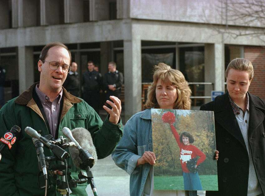 Robert Wood, left, father of murder victim 12-year-old Sara Anne Wood, addresses members of the media as Sara's mother Frances Wood, center, and sister Nikki Wood, 18, look on outside the MCI-Concord Prison in Concord, Mass., Wednesday, March 4, 1998. The Wood family members, all of Frankfort, N.Y., placed flowers and a sign in front of the prison. The family hopes to find the location of Sara's grave from Lewis Lent Jr., who is behind bars at the prison and who confessed earlier to killing the girl.(AP Photo/Steven Senne)