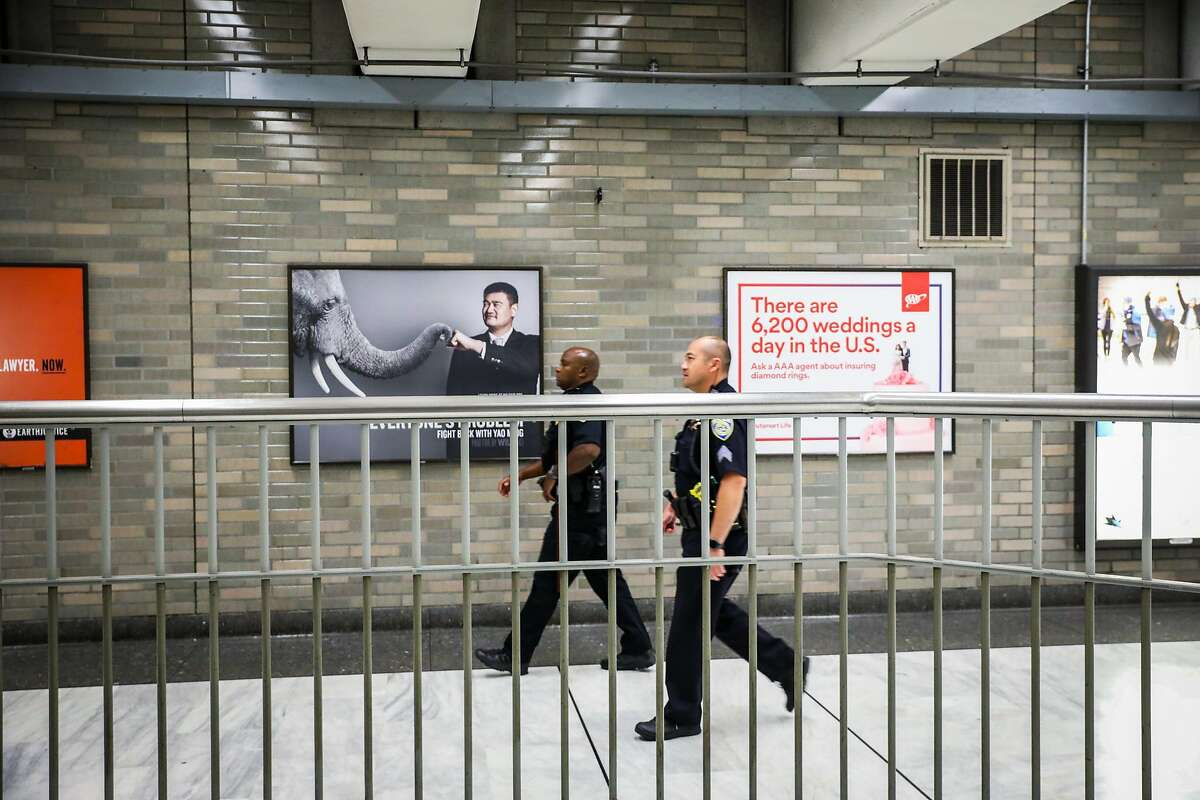 Police officers survey the BART station at Civic Center as they pass a gate that has recently been installed to deter fare evasion in San Francisco, California, on Thursday, Aug. 16, 2018.