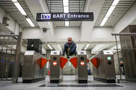 A man jumps the turnstile at the BART station at Civic Center despite gates that were installed (seen at left and right) to deter fare evasion in San Francisco. Photo: Gabrielle Lurie / The Chronicle