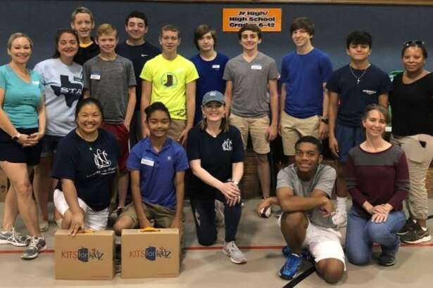 Kingwood Young Men's Service League members and mothers pause for a photo while volunteering at a Back to School drive.