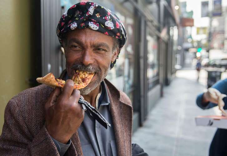 Edward Lee Truman Kennedy, a homeless man, eats a slice of pizza from Nob Hill Pizza & Shawarma given to him by Andrea Carla Michaels in the Nob Hill district of San Francisco, Calif. Tuesday, Aug. 14, 2018.