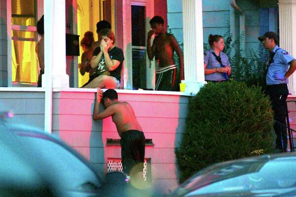 Family and friends gather on a porch after a 2-year-old that was pulled from a backyard pool on Thursday. The child died at a local hospital police officials said. The child was taken out of the water from a residence on Charron Street in Bridgeport, Conn., around 7:25 p.m.