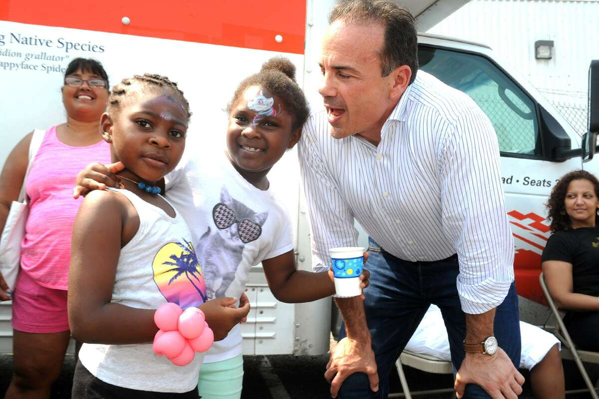 Mayor Joe Ganim is greeted by Denique Hudson, left, and Shadia Bowen during the ?
