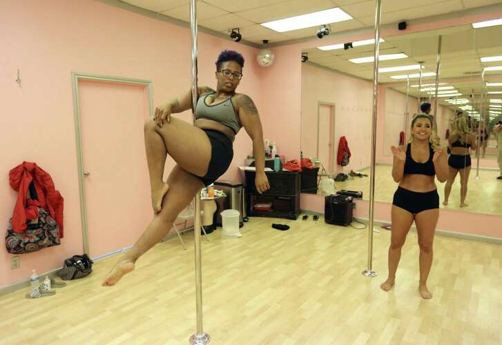 Soft Sensuous Moves pole fitness student Shanel Watkins practices a move while instructor Carla Wetzel encourages her. Watkins is a full-time student at the University of Texas at San Antonio and has been in the pole-dancing class for eight months.