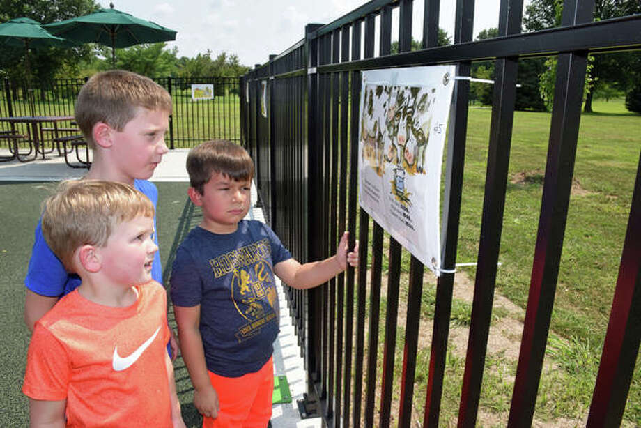Brothers Benjamin Sykes, 5 and Jacob Sykes, 7, both of Godfrey, and four-year-old Deacon Van Nath of Bethalto read one of the StoryWalk pages at Gordon Moore Park in Alton. Photo:       David Blanchette | For The Telegraph
